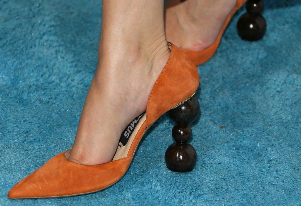 O pereche de pantofi cu toc scurt de culoare piersicie în timp ce se află pe o podea albastră și au tocul compus din sfere suprapuse