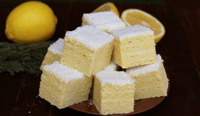 Bucăți de prăjitură Albă ca Zăpada, așezate o farfurie, alături de lamâi întregi și secționate.