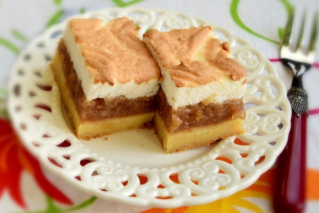 Două porții de prăjitură cu mere și bezea pe o farfurie albă