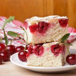 Prăjitură cu vișine și iaurt porționată pe o farfurie albă