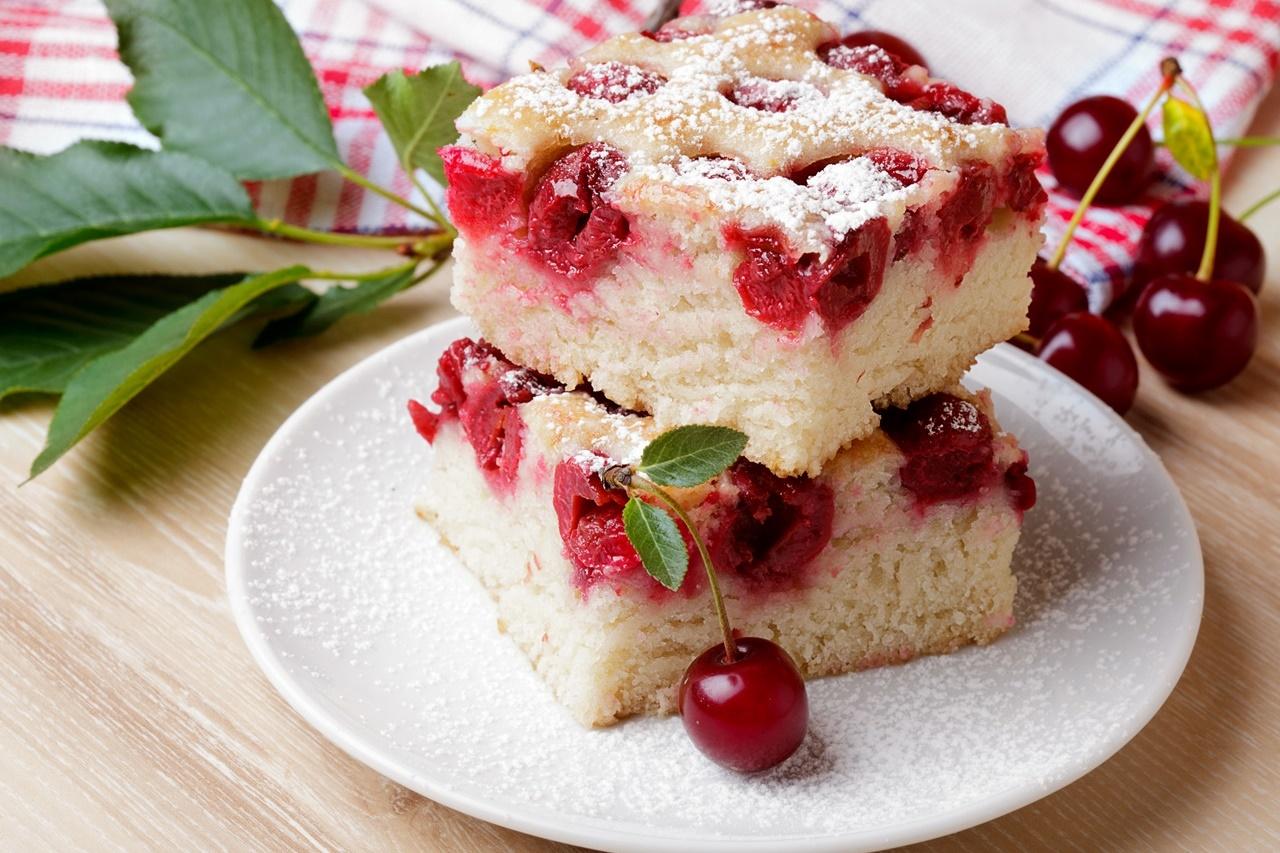 Două porții de Prăjitură cu vișine și iaurt pe un platou alb
