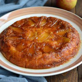 Prăjitură cu mere caramelizate pe un platou alb cu margini maro