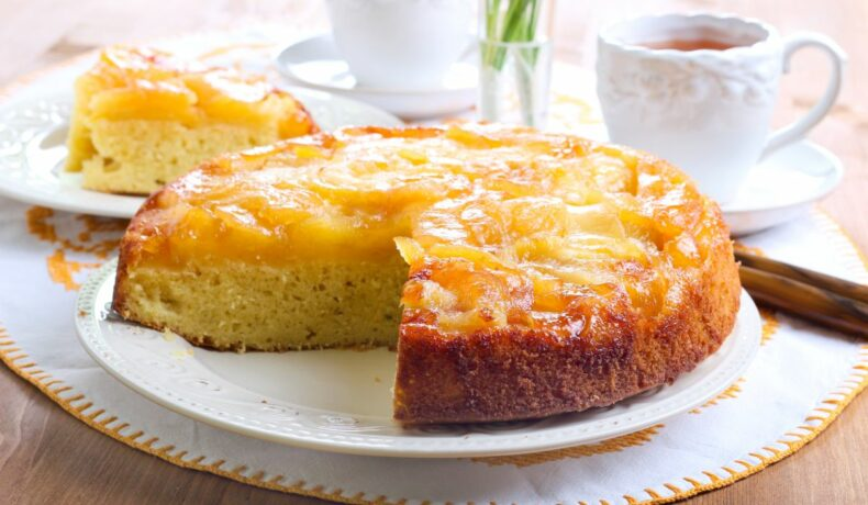 Prăjitură răsturnată cu mere caramelizate, așezată pe un platou albă și tăiată în secțiune.