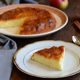 Prăjitură răsturnată cu mere caramelizate, porționată pe o farfurie albă