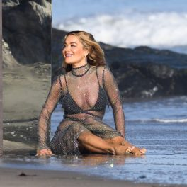 Rita Ora, într-o rochie din plasă, lungă, la plajă, în timp ce filmează un nou videoclip