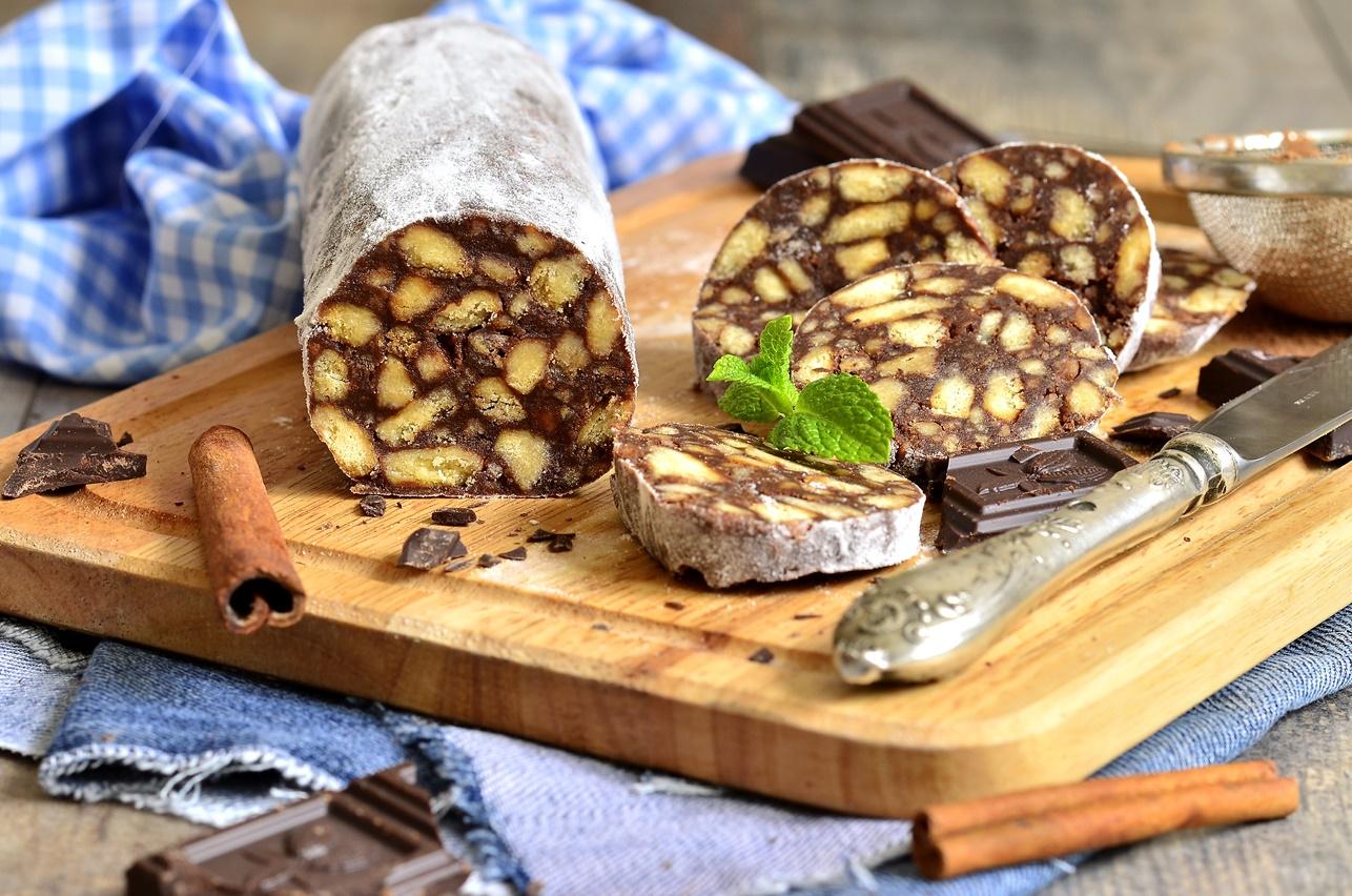 Salam de biscuiți cu ciocolată decorat cu zahăr pudră, pe un suport de lemn