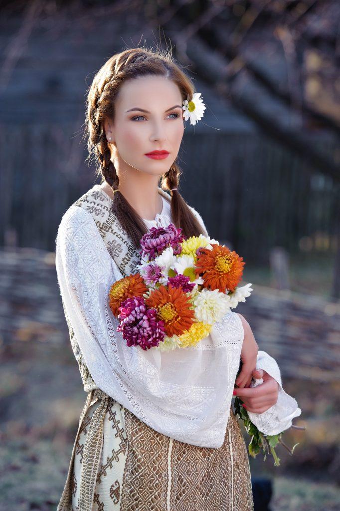 Portret al unei tinere frumoase care își poartă părul împletit în două codițe și este îmbrăcată în port tradițional românesc pentru a celebra mai multe tradiții de sânziene