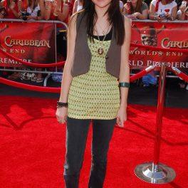 Selena Gomez pe covorul roșu la premiera Piraților din Caraibe din 2007 purtând o pereche de blugi mulați cu o bluză lungă galbenă cu dungi negre peste care a asortat o vestă de culoarea gri