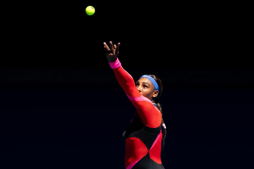 Serena Williams, pe terenul de tenis la Australian Open, în timp ce lovește mingea cu racheta de tenis