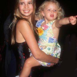 Tiffany Trump, imagine din copilărie, în brațe, cu părul desfăcut, în timp ce arată cu degetul