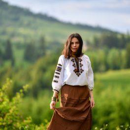 O tânără frumoasă purtând un costum tradițional românesc în timp ce se află pe o pajiște verde