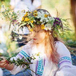 O fetiță blondă frumasă care poartă o ie și o coroniță de flori pe cap