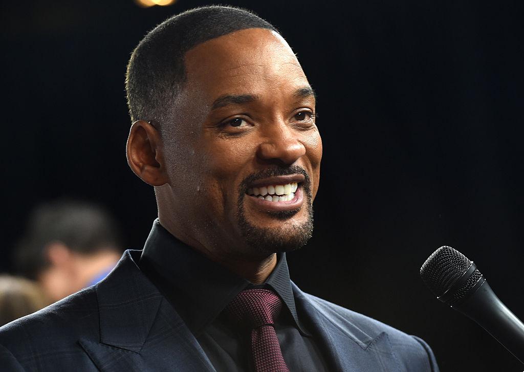 Will Smith, la gala Concussion, îmbrăcat elegant, într-un costum negru, zâmbind în fața camerei