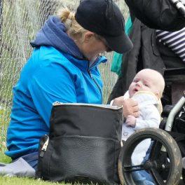 Zara Tindall, în timp ce se joacă cu bebelușul ei pe iarbă, la un concurs de echitație