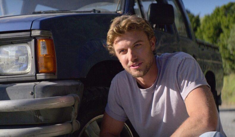 Adam în fața unei mașini în timp ce apare într-una din scenele din filmul Falling Inn Love