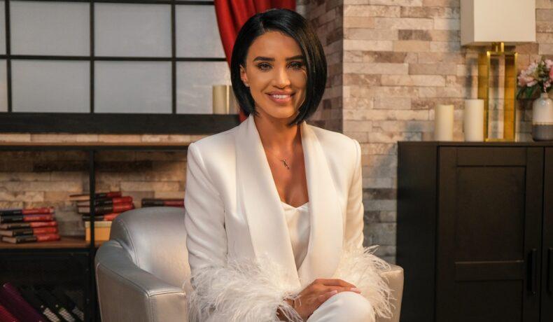 Adelina Peștrițu purtând un costum în întregime alb și zâmbind la cameră în timp ce stă pe un scaun argintiu la interviul oferit pentru Catine.ro