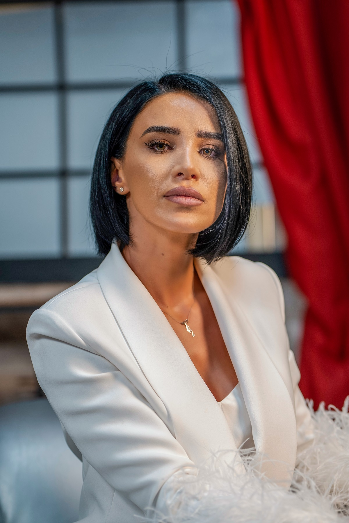 Portret al Adelinei Pestrițu într-un costum alb în timp ce privește camera de fotografiat