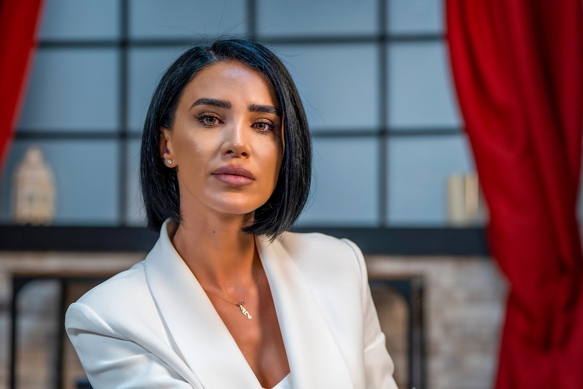 Adelina Pestrițu în timp ce privește la cameră, poartă un sacou alb și sta pe un scaun argintiu la interviul pentru Catine