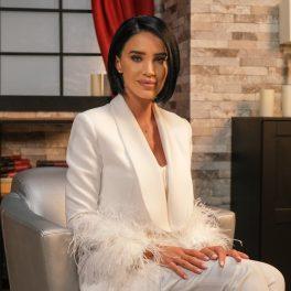Adelina Peștrițu în timp ce stă pe un scaun cu mâinile pe genunchi și purtând un costum în întregime alb