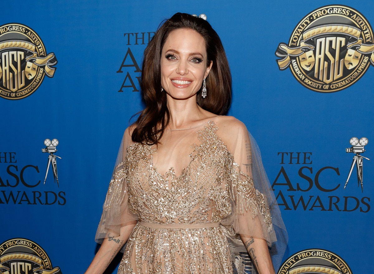 Angelina Jolie purtând o rochie bej cu paiete și zâmbind camerelor