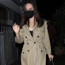 Actrița Angelina Jolie într-un palton bej și purtând mască de protecție în timp ce părăsea un restaorant italienesc din Los Angeles