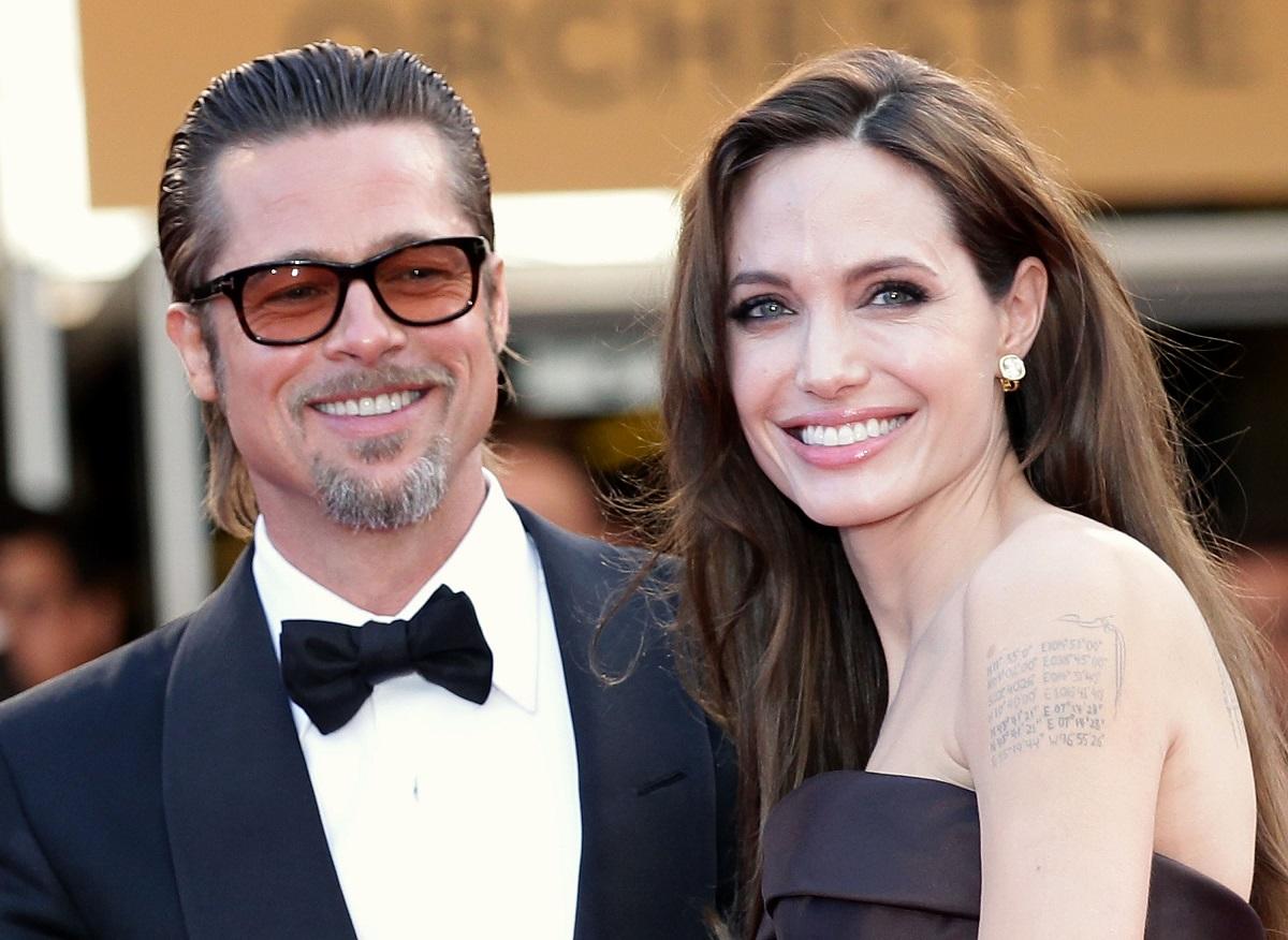 Angelina Jolie într-o rochie neagră în timp ce zâmbește deoarece a obținut o nouă victorie în fața lui Brad Pitt, fiind alături de fostul soț la Festivalul de Film de la Cannes din 2011