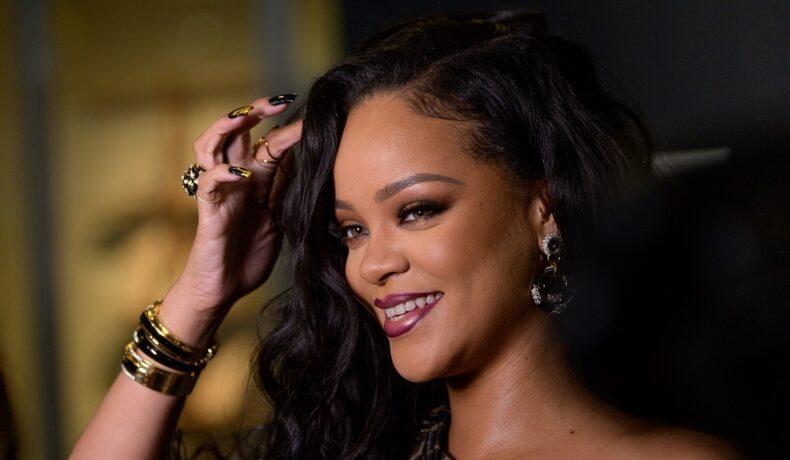 Portret al artistei Rihanna în timp ce își așează părul cu o mână încărcată de inele la lansarea autobiografiei din 2019