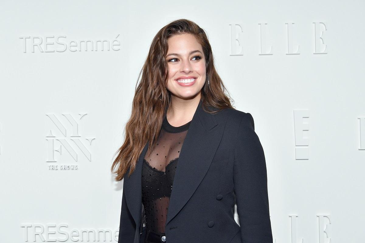 Modelul plus-size Ashley Grahamîntr-un sacou negru și un body transparent în timp ce zâmbește la cameră la un eveniment privat din New York