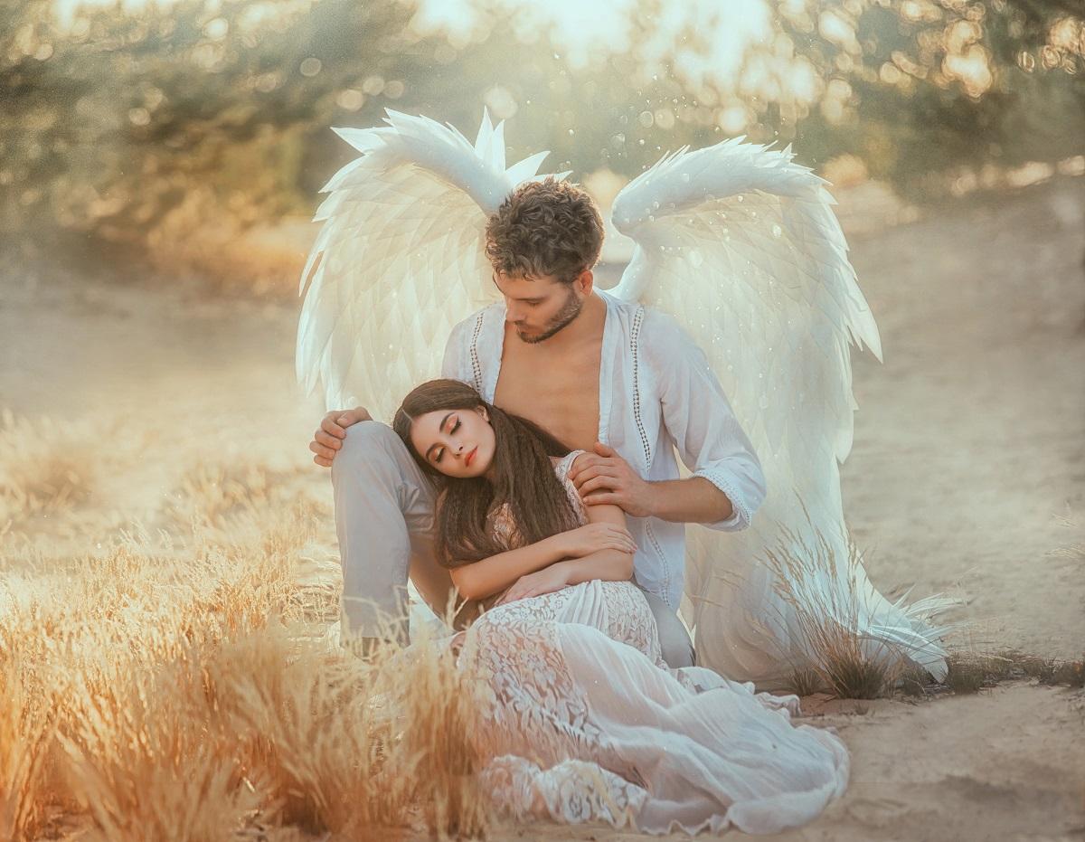 Unul din bărbații care fac femeile cu adevărat fericite, având aripi de înger și stând în genunchi în timp ce o ține după umeri pe iubita sa frumoasă care poartă o rochie albă diafană