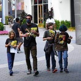 Ben Affleck cu mască pe față alături de copiii săi, Seraphine și Samuel și unul din copiii lui Jennifer Lopez Emme, în timp ce merg într-un parc tematic de distracții