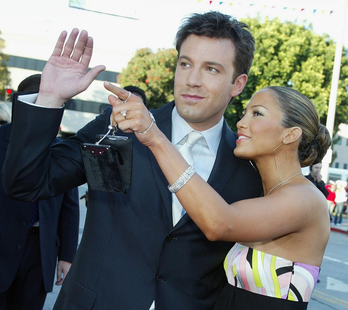 Ben Affleck la costum în timp ce este alături de Jennifer Lopez în rochie care îi arată un lucru în zare la premiera filmului Daredavil din 2003