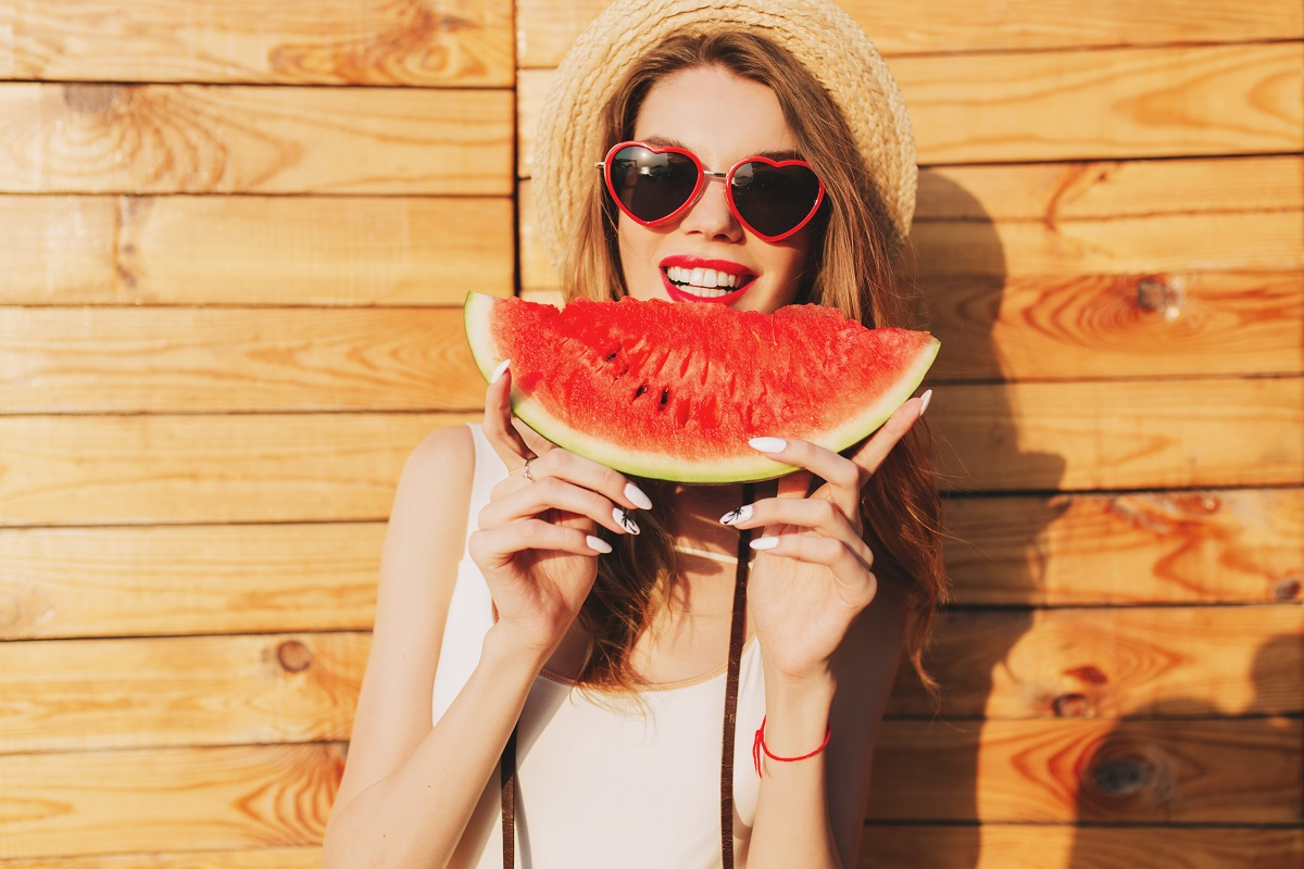 O femeie frumoasă cu ochelari de soare și pălărie de plajă care ține în mâini o felie de pepene și vrea să muște din ea deoarece a aflat care sunt acele beneficii ale consumului de pepene roșu