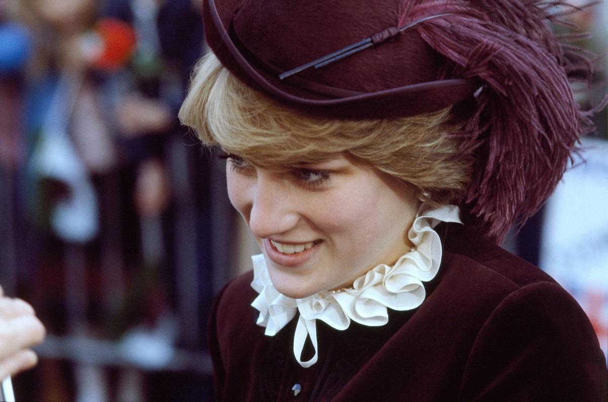 Portret al Prințesei Diana în timp ce poartă o pălărie și un costum violet și zâmbește publicului