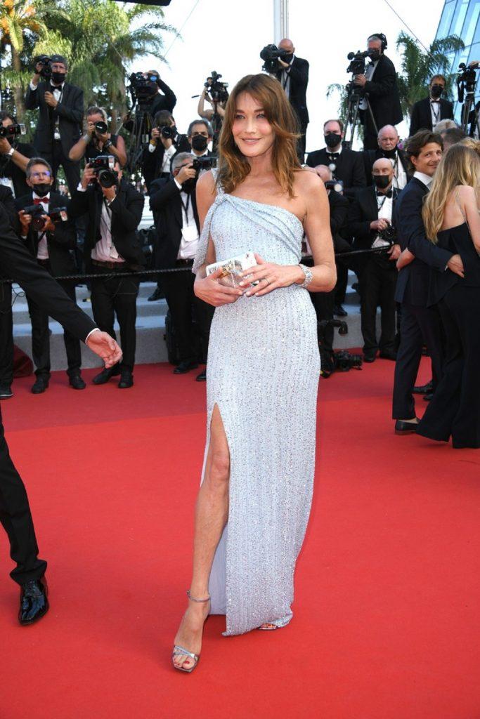 Carla Bruni pe vocorul roșu în timp ce zâmbește la cameră și poartă o rochie Celline la Festivalul de Film de la Cannes