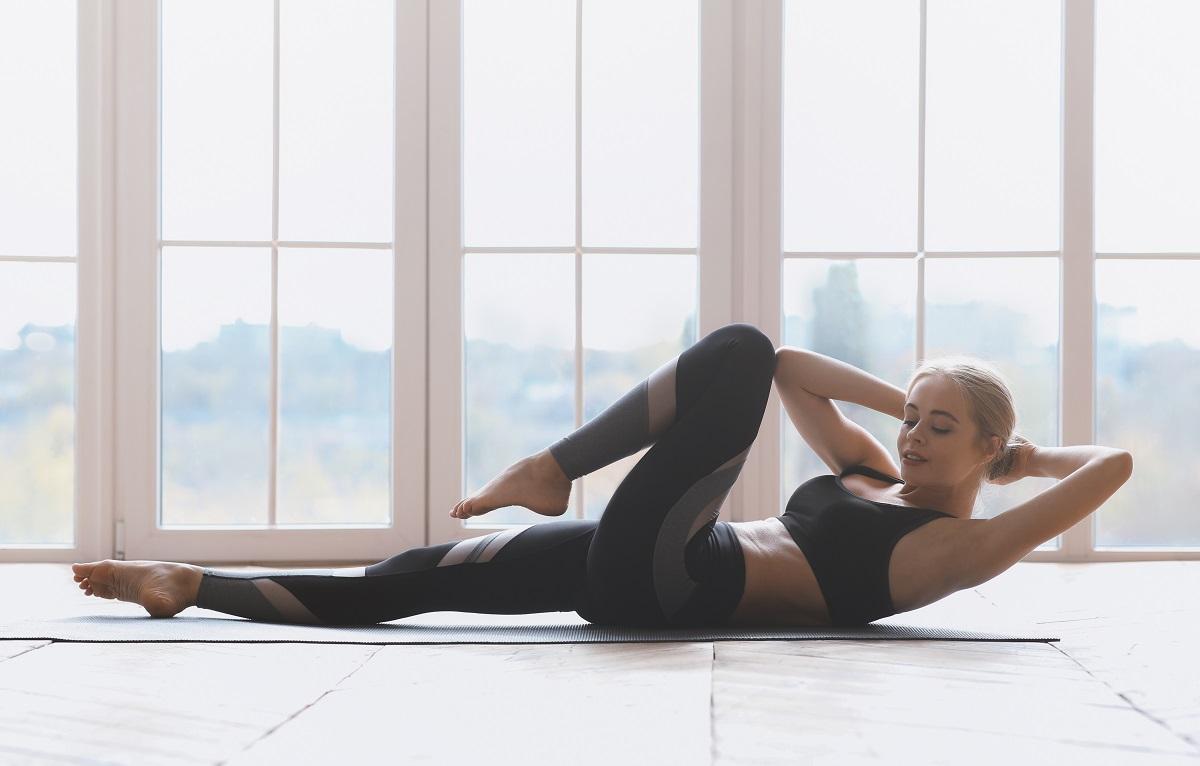 O femeie frumoasă în costum de sport în timp ce face unele dintre cele mai bune exerciții pentru un abdomen plat