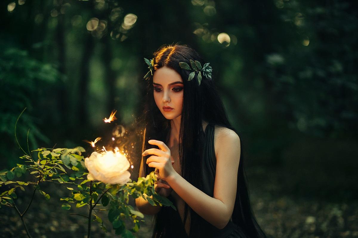 Un cadru feeric cu o pădure verde întunecată și o zână în timp ce privește un trandafir luminat pentru că este una dintre cele mai norocoase zodii ale lunii august 2021