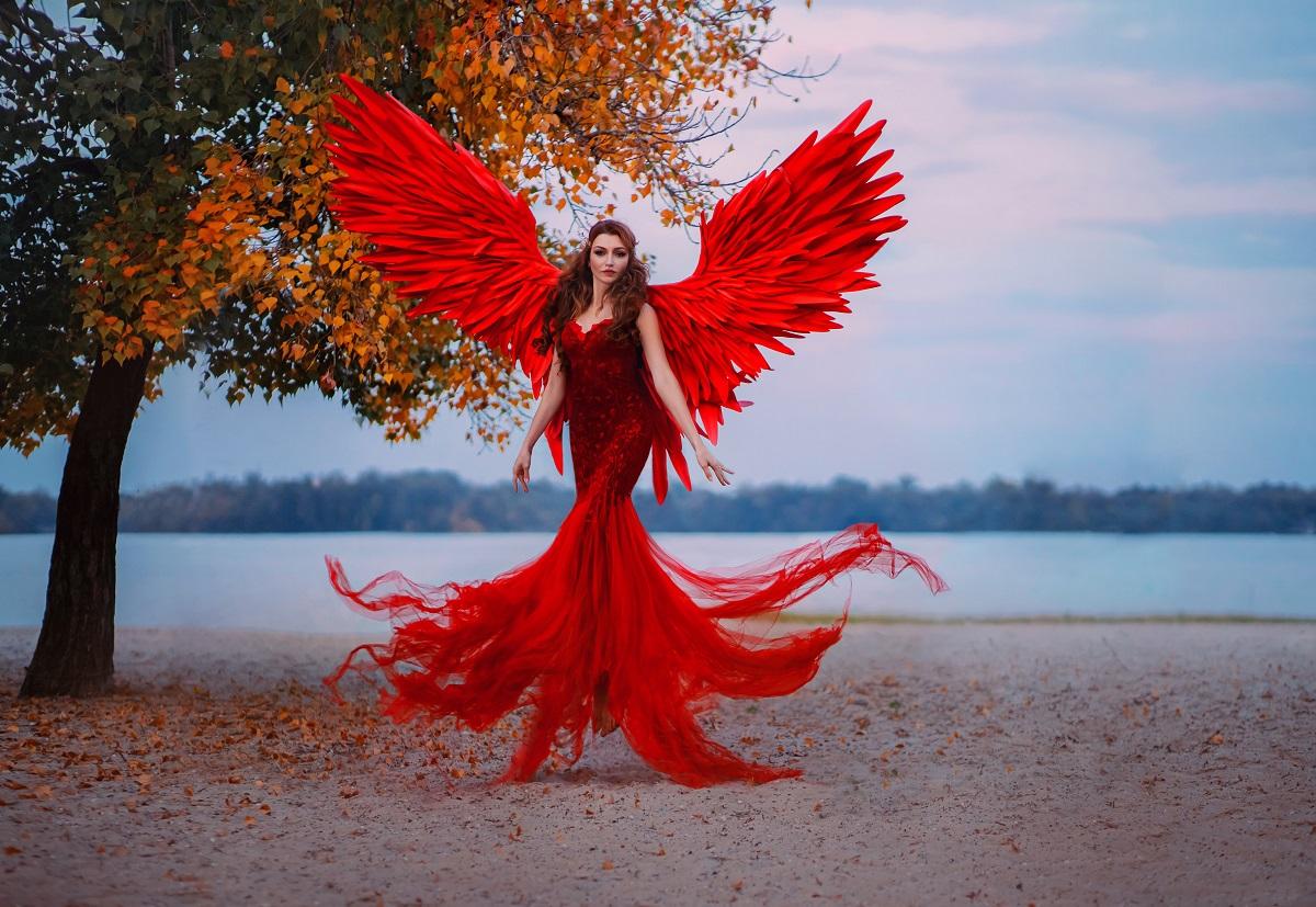 Un cadru feeric din fața unui lac unde se află o femeie superbă cu rochie roșie și aripi de înger roșii pentru a demonstra că este una dintre cele mai pasionale femei din zodiac