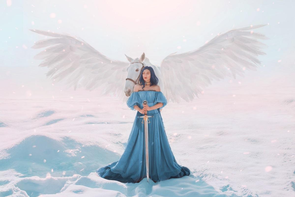 O femeie frumoasă care poartă o rochie albastră vaporoasă în timp ce stă în zăpadă și ține în mâini o sabie și este sprijinită de un cal înaripat pentru a simboliza că este una dintre cele mai puternice femei din zodiac