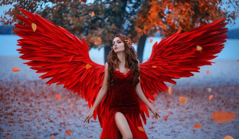 O femeie frumoasă într-un cadru feeric care poartă o rochie roșie cu aripi de înger roșii pentru a demonstra că este una dintre cele mai senzuale femei ale zodiacului
