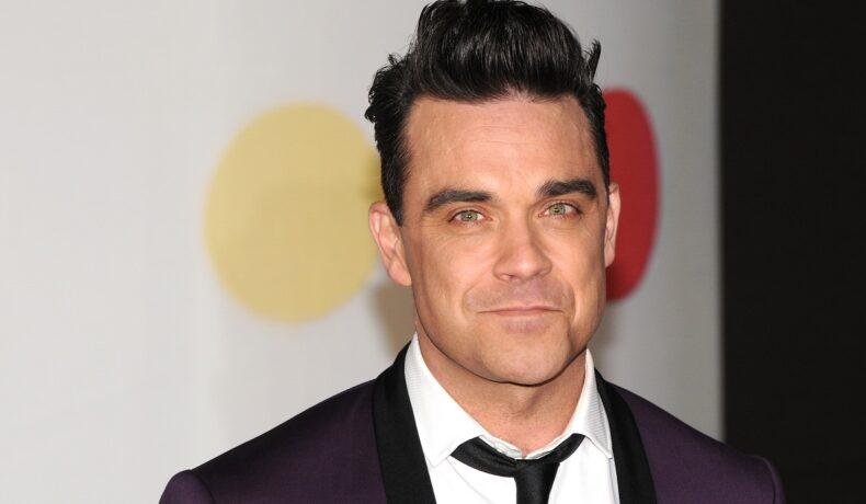 Robbie Williams pe covorul roșu de la Premiile Bit, în anul 2013. Imbrăcat în costum negru, cămașă albă, fundal alb