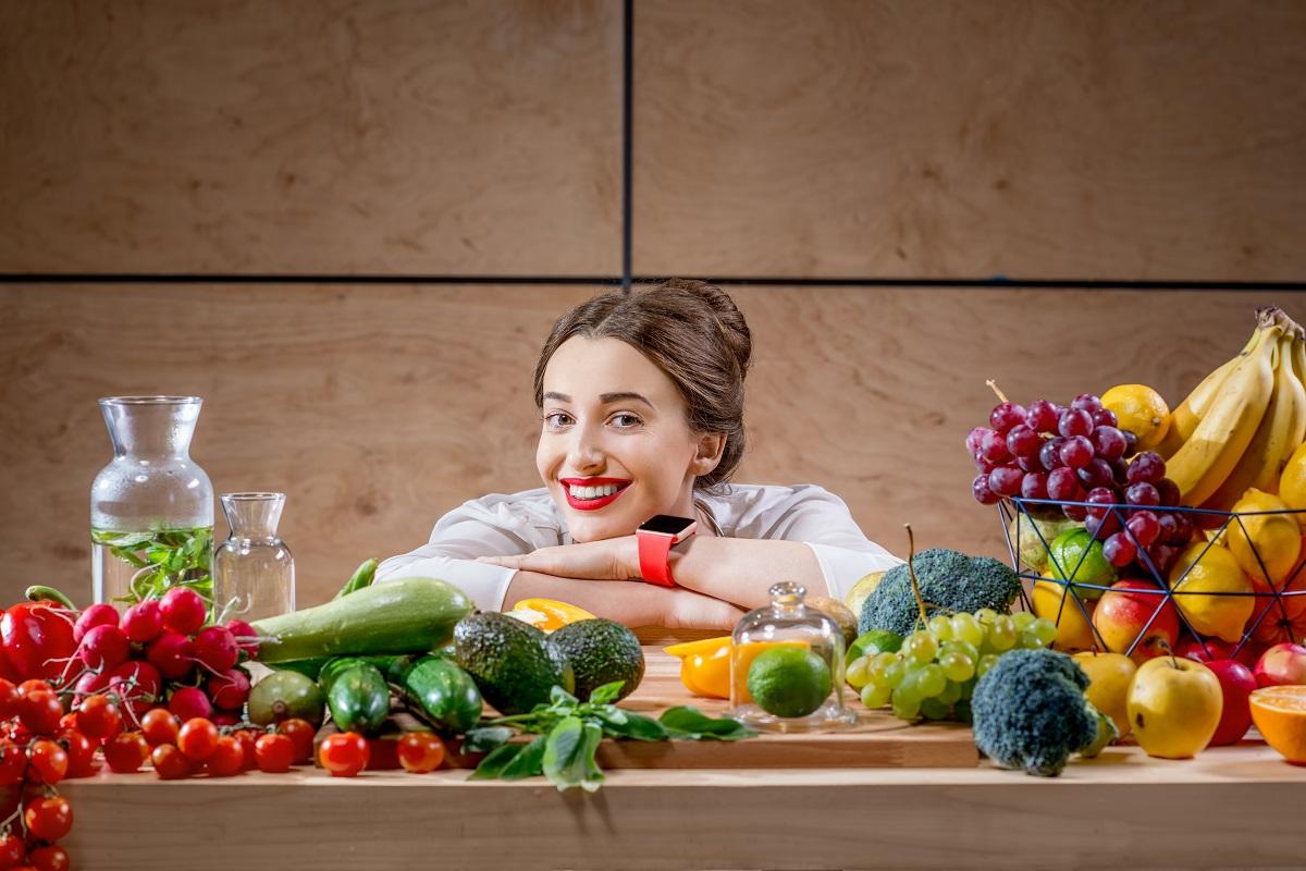 O femeie frumoasă cu părul șaten prins care stă cu mâinile pe masă și cu capul sprijnit pe ele în timp ce se uită la fructele și legumele de pe masă și se gândește la miturile privind consumul fructelor noaptea