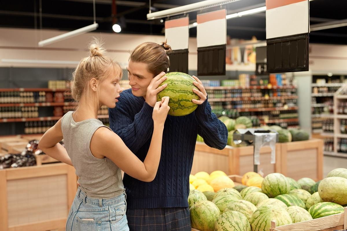 Un culplu de tineri care țin ridicat în mână un pepene și învață cum să alegi pepenele roșu perfect