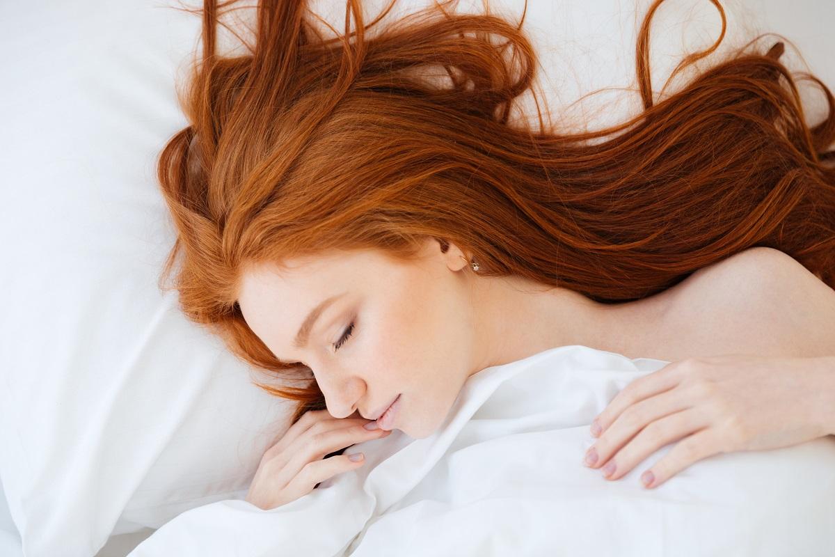 O femeie frumoasă cu părul roșct care doarme și este acoperită cu așternuturile albe
