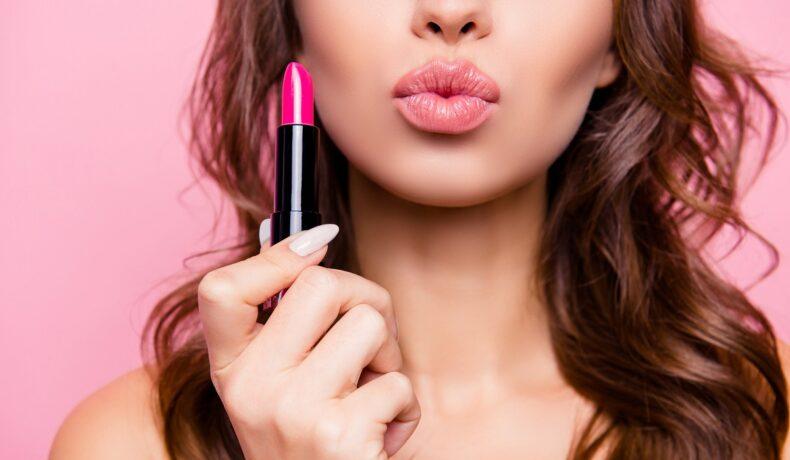 O femeie frumoasă care ține în mână un ruj roz și buzele țuguiate într-un sărut pentru a demonstra cum să aplici corect rujul dacă ai buzele subțiri