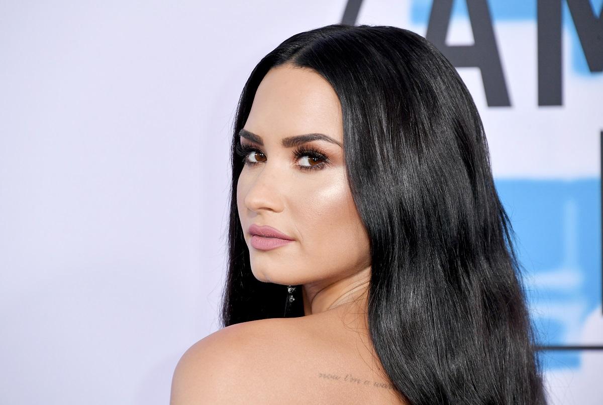 Demi Lovato cu părul lung în timp ce privește peste umăr la American Music Awards în 2017 și care a trimis un mesaj emoționant fanilor pentru a le mulțumi
