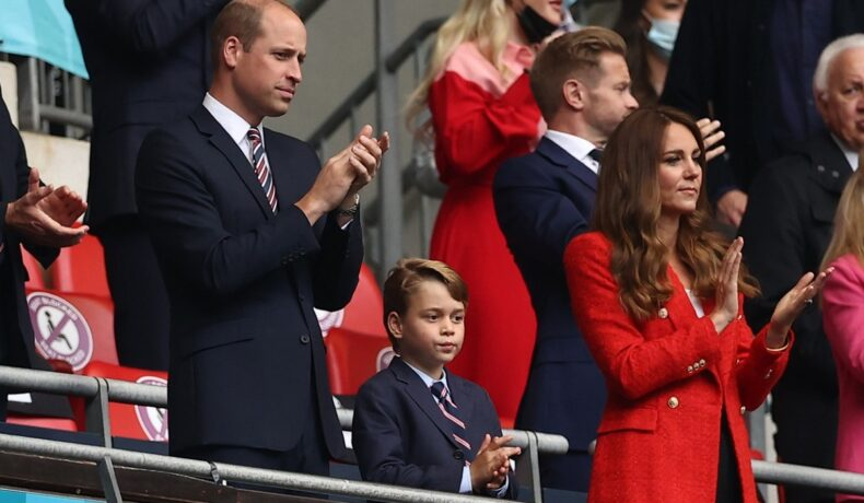 Prințul William alături de Prințul George și Ducesa Kate Middleton într-o tribună la un stadion din Anglia în timp ce aplaudă jucătorii de fotbal