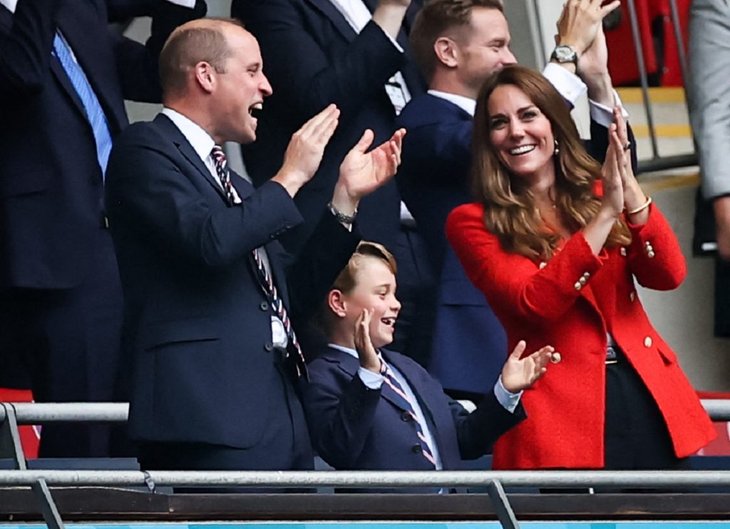 Prințul William alături de Prințul George care a purtat un costum elegant și Ducesa Kate Middleton în timp ce se află în tribuna unui stadion de fotbal și privesc un meci de la Euro 2020