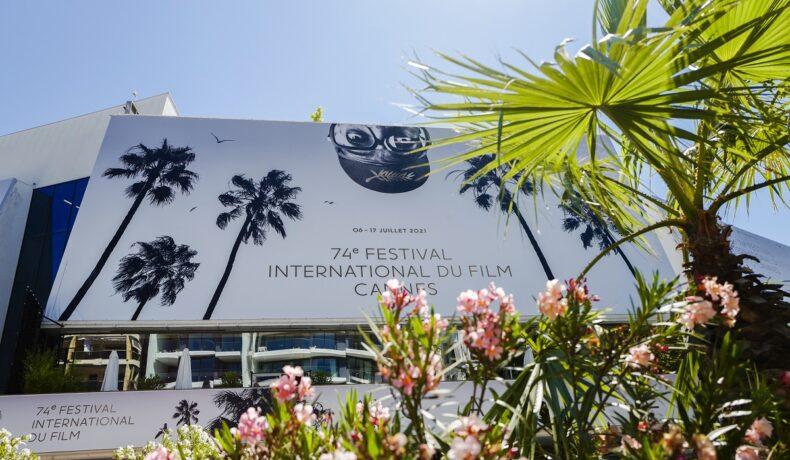 Imagine boemă a afișului de la Festivalul de Film de la Cannes din 2021 acoperit de frunze de palmier și de flori roz