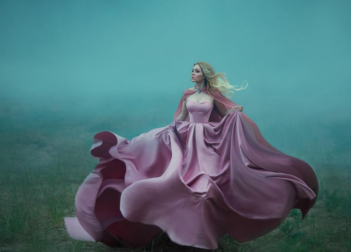 Un ambient înfricoșător în care se află o femeie superbă blondă într-o rochie vaporoasă roz în timp ce fuge și încearcă să ilustreze fricile semnelor zodiacale