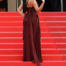 Georgina Rodriguez urcând scările pe covorul roșu în timp ce face cu mâna publicului la Festivalul de Film de la Cannes din 2021